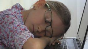 Bambino degli occhiali che dorme sul computer portatile, taccuino, ragazza miope allo scrittorio immagini stock libere da diritti
