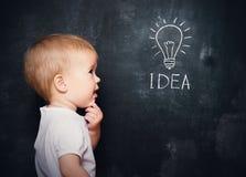 Bambino del bambino alla lavagna con le idee di simbolo della lampadina disegnate gesso Fotografia Stock Libera da Diritti