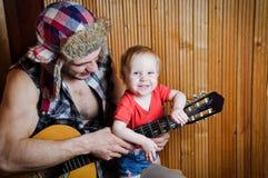 Bambino del bambino con suo padre dei pantaloni a vita bassa che gioca chitarra su fondo di legno Fotografia Stock Libera da Diritti