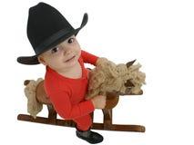 Bambino del cowboy con il cappello nero su un cavallo di oscillazione Immagini Stock