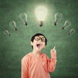 Bambino del genio che indica alla lampadina della luce intensa Fotografia Stock Libera da Diritti