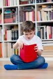 Bambino del ragazzino che legge un libro rosso nella biblioteca Fotografia Stock Libera da Diritti