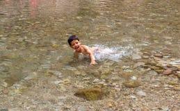 Bambino del ragazzo che gioca nel fiume Fotografie Stock