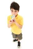 Bambino del ragazzo che per mezzo dell'inalatore di asma con l'alloggiamento del distanziatore immagine stock