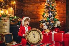 Bambino del ragazzo di Santa piccolo celebrare natale a casa Festa della famiglia Gioco da bambini del ragazzo vicino all'albero  immagine stock