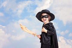 Bambino del supereroe con sward e costume su un fondo del cielo blu Fotografia Stock