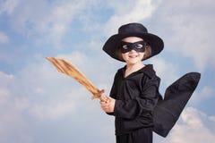 Bambino del supereroe con sward e costume su un fondo del cielo blu Fotografia Stock Libera da Diritti