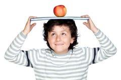 Bambino dell'allievo con un libro sopra la sua testa Fotografia Stock