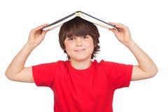 Bambino dell'allievo con un libro sopra la sua testa Fotografie Stock
