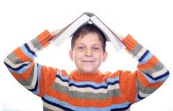 Bambino dell'allievo con un libro sulla sua testa Immagini Stock Libere da Diritti