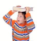 Bambino dell'allievo con un libro sulla sua testa Fotografia Stock Libera da Diritti