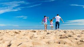 Bambino dell'oscillazione dei genitori sulla spiaggia Fotografia Stock
