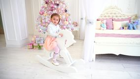 Bambino della bambina che gioca nella stanza del ` s dei bambini sull'albero di Natale rosa del fondo con i giocattoli stock footage