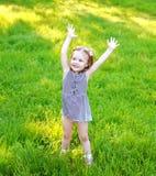 Bambino della bambina divertendosi sull'erba di estate soleggiata Fotografie Stock Libere da Diritti