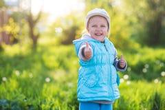 Bambino della bambina in un campo con erba verde ed il tulipano di fioritura fotografie stock libere da diritti