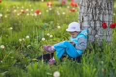 Bambino della bambina in un campo con erba verde ed il tulipano di fioritura immagine stock libera da diritti
