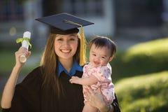 Bambino della holding del laureato della giovane donna Fotografia Stock