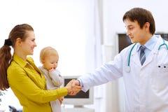 Bambino della holding della madre e doct pediatrico di handshaking immagini stock libere da diritti