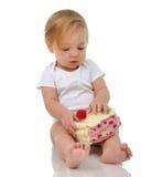 Bambino della neonata del bambino che si siede tenendo pezzo di giocattolo del dolce della caramella Fotografie Stock