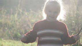 Bambino della ragazza che gioca con i rami stock footage