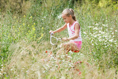 Bambino della ragazza che guida una bicicletta, fiori nel campo Immagine Stock Libera da Diritti