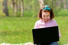 Bambino della ragazza con il computer portatile all'aperto Immagine Stock Libera da Diritti