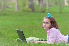 Bambino della ragazza con il computer portatile all'aperto Fotografia Stock
