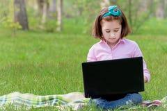 Bambino della ragazza con il computer portatile all'aperto Fotografie Stock Libere da Diritti