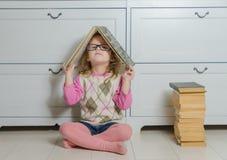 Bambino della ragazza con un libro con i vetri che si siedono sul pavimento Immagini Stock