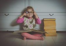 Bambino della ragazza con un libro con i vetri che si siedono sul pavimento, Fotografia Stock
