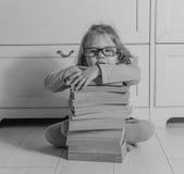 Bambino della ragazza con un libro con i vetri che si siedono sul pavimento, in bianco e nero Immagini Stock