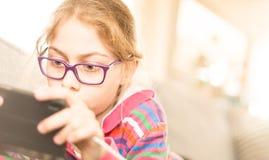 Bambino della ragazza del bambino che gioca gioco sul telefono cellulare a casa Fotografie Stock