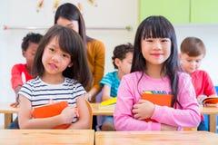 Bambino della ragazza di due asiatici che abbraccia libro e che sorride nell'aula e nel whi Immagine Stock