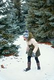Bambino della ragazza divertendosi nella foresta di inverno, bello paesaggio con gli abeti nevosi fotografia stock