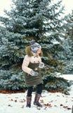 Bambino della ragazza divertendosi nella foresta di inverno, bello paesaggio con gli abeti nevosi immagini stock