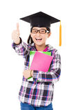 bambino della scuola in cappuccio di graduazione con il pollice su Fotografia Stock