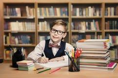 Bambino della scuola che studia nella biblioteca, libro di scrittura del bambino, scaffali Immagine Stock