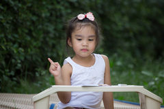 Bambino della scuola primaria che pensa alla risposta che si siede al suo scrittorio Fotografia Stock