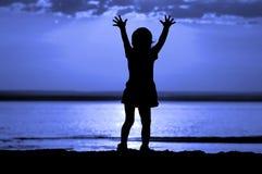 Bambino della siluetta sulla notte della luna Fotografia Stock