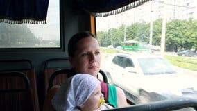 Bambino della tenuta della mamma sulle mani e sui giri il bus archivi video