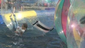 Bambino dentro la grande palla gonfiabile sulla superficie dell'acqua video d archivio