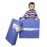Bambino dentro un contenitore di regalo isolato su un fondo bianco Immagine Stock