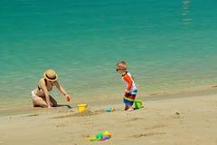 Bambino di due anni che gioca con la madre sulla spiaggia Fotografie Stock