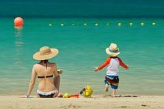 Bambino di due anni che gioca con la madre sulla spiaggia Fotografia Stock