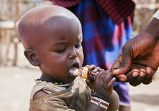 Bambino di Maasai che prova una lecca-lecca in Tanzania, Africa Immagini Stock Libere da Diritti