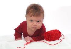 Bambino di menzogne con il clew rosso delle lane Fotografie Stock