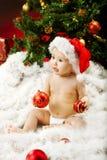 Bambino di natale in cappello su pelliccia che tiene sfera rossa Fotografia Stock
