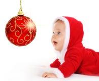 Bambino di natale che esamina una sfera rossa scintillante Fotografia Stock Libera da Diritti