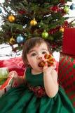 Bambino di Natale che mangia i biscotti Immagine Stock