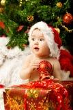 Bambino di natale che tiene sfera rossa vicino al contenitore di regalo Fotografia Stock Libera da Diritti